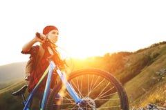 Touriste de femme sur une bicyclette au sommet de montagne au coucher du soleil dehors photographie stock