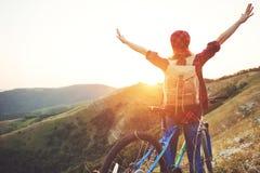 Touriste de femme sur une bicyclette au sommet de montagne au coucher du soleil dehors photo libre de droits