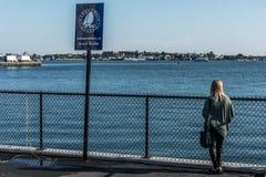 Touriste de fille tenant la promenade proche de panorama de port de Boston de signe de courrier d'isolement sur un quai long enso images libres de droits