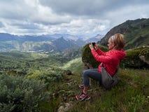 Touriste de jeune femme avec le sac à dos se reposant sur le bord du ` s de falaise et merci Images libres de droits