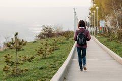 Touriste de jeune femme marchant sur la route en parc blanc d'isolement de vue arrière photographie stock libre de droits