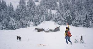 Touriste de jeune homme dans la campagne au milieu de la montagne marchant par le champ neigeux ? deux chevaux, ? cot? d'a banque de vidéos