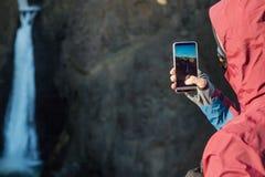Touriste de type prenant des photos d'une cascade dans les montagnes d'I Image stock