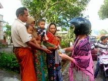 Touriste donnant une sucrerie à la famille locale Image libre de droits