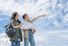 Touriste employant une carte pour l'emplacement de découverte sous le ciel bleu Image stock