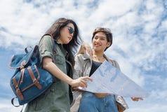 Touriste employant une carte pour l'emplacement de découverte sous le ciel bleu Photographie stock