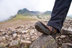 Touriste en augmentant des chaussures placé sur la montagne Photographie stock libre de droits