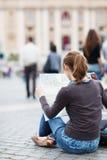 Touriste féminin assez jeune étudiant une carte images libres de droits