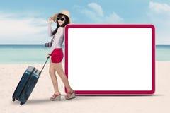 Touriste féminin avec l'enseigne à la côte Photographie stock libre de droits