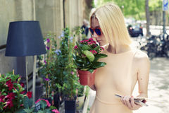 Touriste féminin avec la carte de ville tenant le pot de fleurs rouges au jour ensoleillé de récréation en été dehors Photos libres de droits