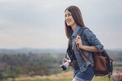 Touriste féminin avec le sac à dos et la caméra dans la campagne photo libre de droits