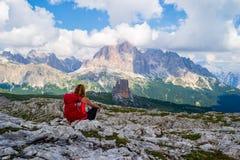 Touriste féminin avec le sac à dos rouge faisant une pause sur le plateau de roche au-dessous de Rifugio Nuvolau, dolomites, et r image stock
