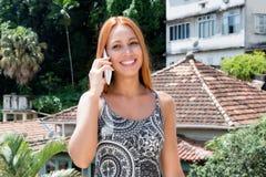 Touriste féminin avec les cheveux rouges parlant avec l'ami au téléphone Image libre de droits