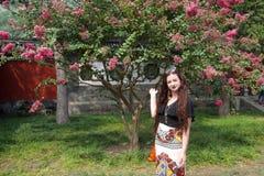 Touriste féminin caucasien de brune aux cheveux longs posant avec la fleur rose photo stock