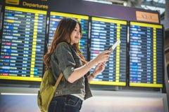 Touriste féminin de beauté regardant des programmes de vol pour vérifier t photos stock