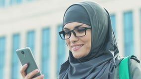 Touriste féminin musulman employant le navigateur dans le téléphone, interdiction de voyage pour les femmes islamiques banque de vidéos