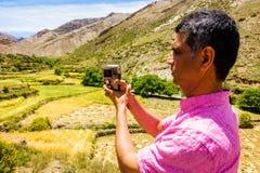 Touriste filmant une vallée dans les montagnes d'atlas Photo libre de droits