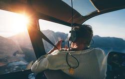 Touriste féminin en tournée d'hélicoptère prenant des photos Images stock
