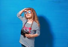 Touriste heureuse de fille d'enfant avec le rétro appareil-photo au mur bleu Photos stock