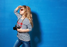 Touriste heureuse de fille d'enfant avec le rétro appareil-photo au mur bleu Photographie stock