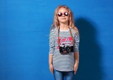 Touriste heureuse de fille d'enfant avec le rétro appareil-photo au mur bleu Image libre de droits