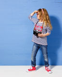 Touriste heureuse de fille d'enfant avec le rétro appareil-photo au mur bleu Photographie stock libre de droits