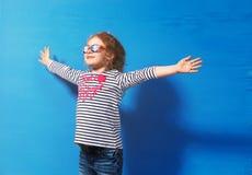 Touriste heureuse de fille d'enfant dans des lunettes de soleil roses au mur bleu Concept de voyage et d'aventure Photo libre de droits