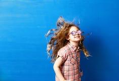 Touriste heureuse de fille d'enfant dans des lunettes de soleil roses au mur bleu Concept de voyage et d'aventure Photographie stock libre de droits