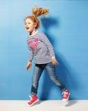 Touriste heureuse de fille d'enfant dans des lunettes de soleil roses au mur bleu Concept de voyage et d'aventure Photographie stock