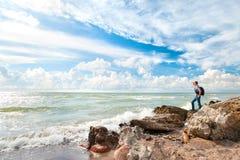 Touriste heureux d'homme se tenant sur la côte et regardant en avant Images libres de droits