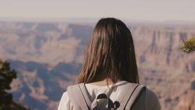 Touriste heureux en gros plan de jeune femme de vue arrière avec le sac à dos observant le panorama épique d'été de Grand Canyon  banque de vidéos