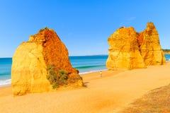 Touriste marchant entre les roches sur la plage Images stock