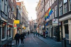 Touriste marchant le long d'une rue étroite de la pièce historique de ville d'Amsterdam Photographie stock