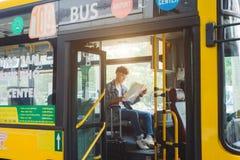 Touriste masculin asiatique s'asseyant dans l'autobus de ville et lisant une carte Photo stock