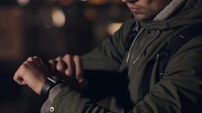 Touriste masculin avec le smartwatch sur la rue de nuit, semblant montre partie et émouvante Photo stock