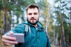 Touriste masculin barbu beau prenant un selfie dans une forêt photos libres de droits
