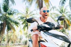 Touriste masculin de sourire heureux dans des lunettes de soleil montant le scooter de motocyclette pendant ses vacances tropical photographie stock libre de droits