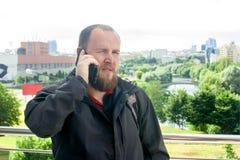 Touriste masculin mûr d'affaires avec une barbe parlant au téléphone photos libres de droits