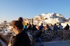 Touriste observant et prenant des photos de coucher du soleil dans le village d'Oia Image libre de droits