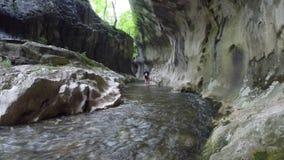 Touriste passant dans l'eau dans un canyon sauvage banque de vidéos