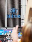 Touriste photographiant le signe de Hilton Hotel, NYC Images libres de droits