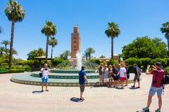 Touriste prenant des photos dans des jardins Marrakech de Koutoubia Image libre de droits
