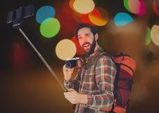 Touriste prenant le selfie avec son appareil-photo et le sien téléphone sur le fond rougeoyant Photographie stock