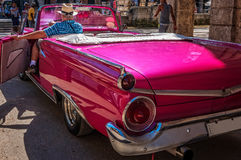 Touriste qui veut découvrir comment il se sent pour conduire une voiture cubaine de vintage Photos libres de droits