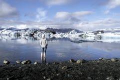 Touriste regardant Jokulsarlon, lagune, Islande Photographie stock libre de droits