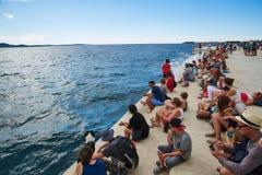 Touriste s'asseyant sur l'organe de mer, Zadar Photographie stock