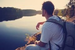 Touriste s'asseyant sur la falaise au-dessus du lac et regardant loin le coucher du soleil Images libres de droits