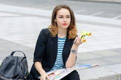 Touriste s'asseyant sur le trottoir avec une carte Photos stock