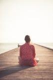 Touriste songeur de femme s'asseyant sur le pilier en bois à la plage pendant le coucher du soleil et regardant la vue d'infini v Image libre de droits