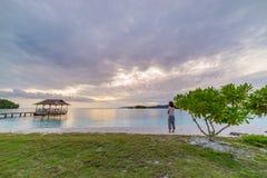 Touriste sur la plage tropicale au coucher du soleil, îles à distance de Togian d'îles de Togean, Sulawesi, Indonésie, destinatio Photo libre de droits